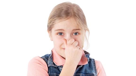 Mädchen hält sich die Nase zu