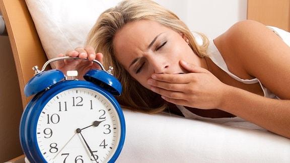 Frau drückt liegend mit einer Hand auf einen Wecker
