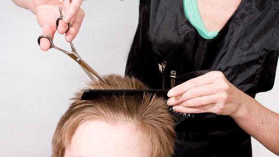 Friseurin schneidet einem Kind die Haare