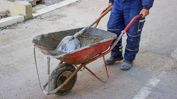 Bauarbeiter schiebt Schubkarre voller Kies