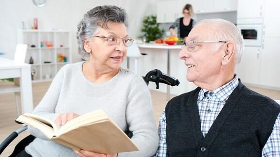 Eine ältere Frau im Rollstuhl sitzt neben einem älteren Mann und liest ihm aus einem Buch etwas vor.