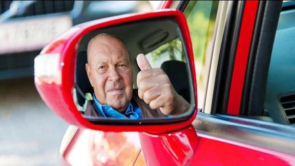 Ein älterer Mann sitzt im Auto und spieglt sich im Seitenspiegel.