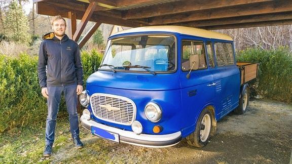 Ein Mann steht neben einem umgebauten und blau lackiertem Barkas, welcher in einem Carport steht.