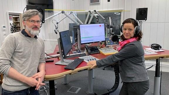 Eine Frau und ein Mann stehen in einem Radiostudio und schauen in die Kamera.