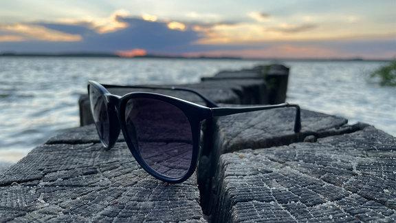 Eine Sonnenbrille liegt auf einer Bune.