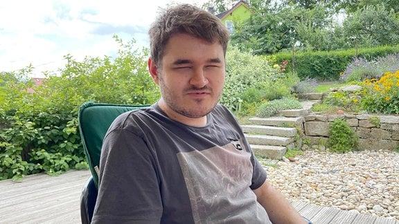 Ein junger Mann sitzt auf einer Terasse.