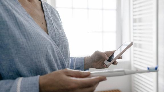 Nahaufnahme einer Frau mit Handy und Zahnbürste im Badezimmer.
