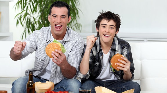 Vater und Sohn sitzen auf dem Sofa, essen Burgen und freuen sich.