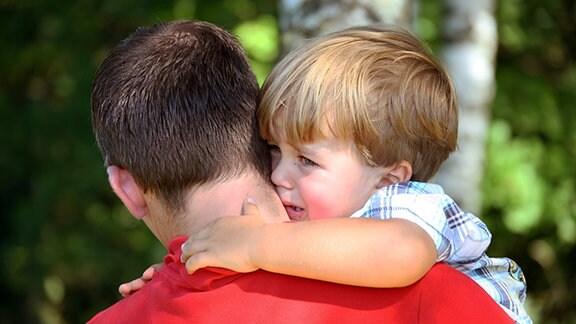 Ein Mann hält ein Kind auf den Arm.