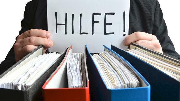 Ein Zettel mit der Aufschrift 'Hilfe' wird hinter Aktenordnern gehalten