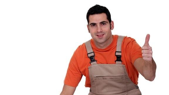 Ein Mann in Latzhose kniet neben einem zusammengerollten Teppich, während er zur Kamera schaut, lächelt und mit seiner linken Hand den Daumen hoch zeigt