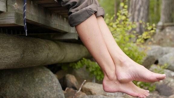 Nackte Füße baumeln bon einem Holzsteg, daneben Wanderschuhe