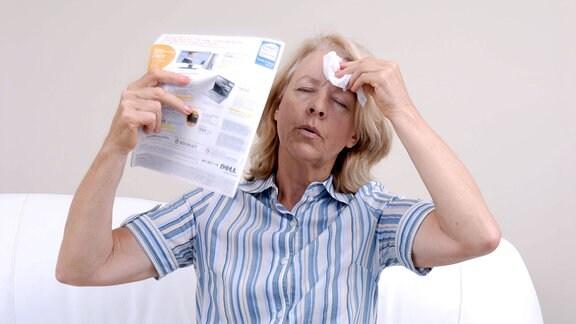 Eine ältere Frau in den Wechseljahren fächelt sich mit einer Illustrierten Luft zu.