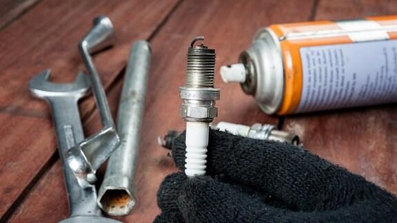 Verrußte Zündkerze in der Hand eines Technikers, daneben Werkzeug und Spraydose
