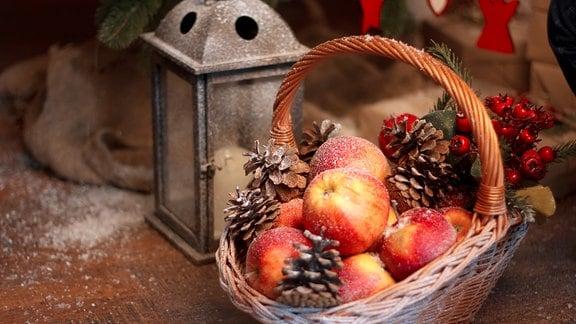 Äpfel mit weihnachtlicher Deko in einem Korb