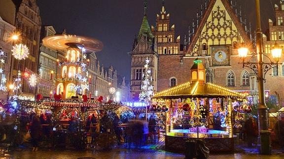 Menschen besuchen abends den Weihnachtsmarkt mit seinen Lichtern und der Pyramide.