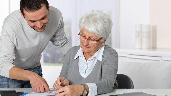 Ein junger Mann steht neben einer älteren Frau, die an einem Tisch sitzt