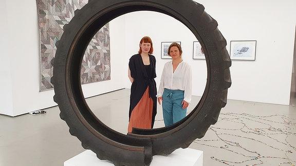 zwei Frauen stehen vor einem Reifen in einer Ausstellung