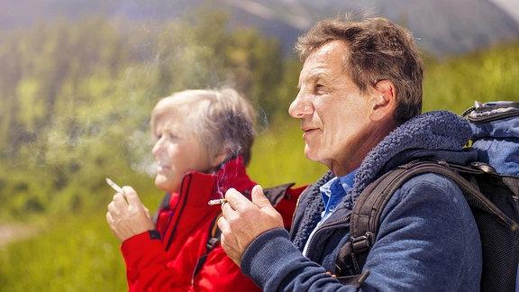 Ein älteres Pärchen raucht während einer Wanderung in den Bergen.