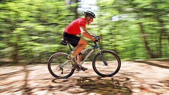 Sportlicher Senior fährt mit dem Mountainbike durch einen Wald