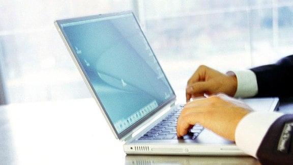 Ein Mann tippt auf einer Notebook-Tastatur