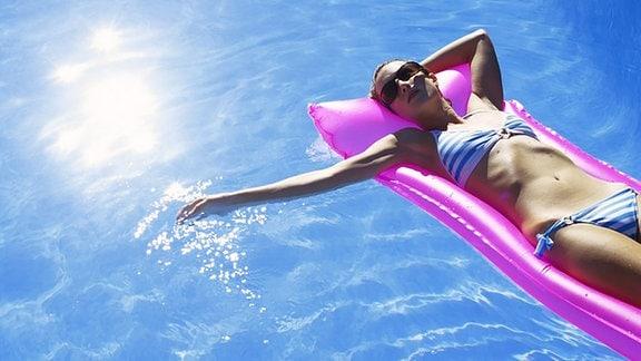 Frau auf einer Luftmatratze in einem Swimming Pool