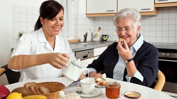 Eine Pflegerin gießt einer Frau Milch in den Kaffee