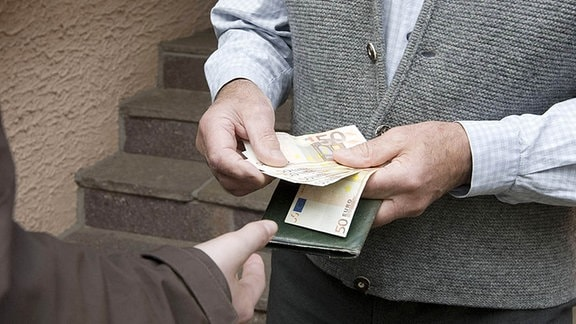 Ein Mann gibt einem Anderen 50-Euro-Scheine