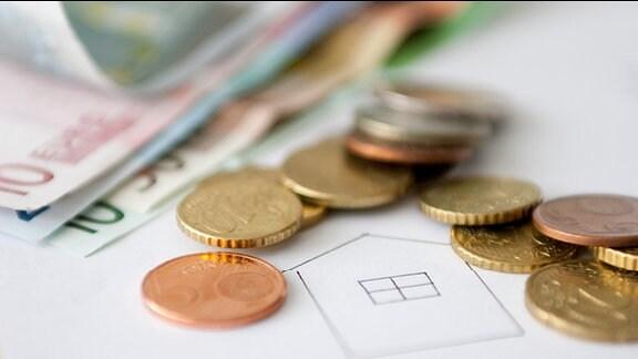 Ein gezeichnetes Haus und Euro-Geldstücke