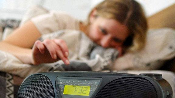 Eine junge Frau bedient ein Radio