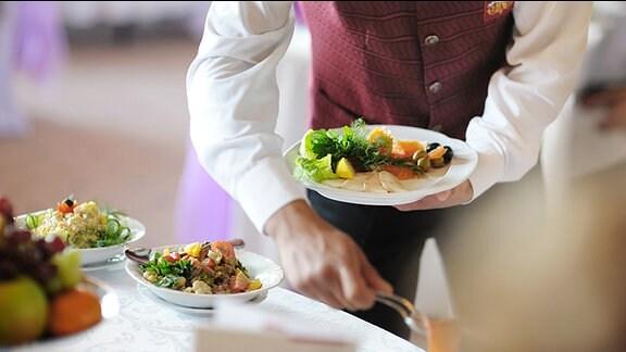 Ein Kellner serviert in einem Restaurant Essen