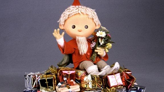 Die Figur des Sandmanns sitzt auf einem Berg Geschenke, hält einen Strauß Blumen und winkt.