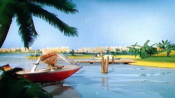 Sandmännchen fährt mit dem Boot über einen Fluss.
