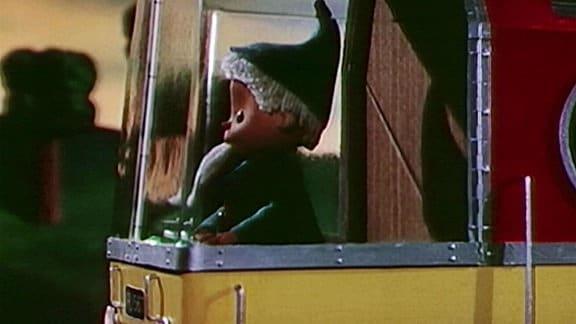 Der Sandmann steht im Lokführerstand eines D-Zuges.