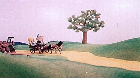 Der Sandmann fährt mit der Kutsche. Neben ihm sitzt ein Mädchen.