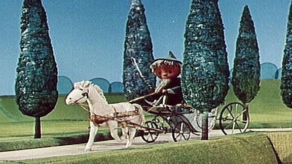 Der Sandmann fährt mit der Kutsche durch den Märchenwald.