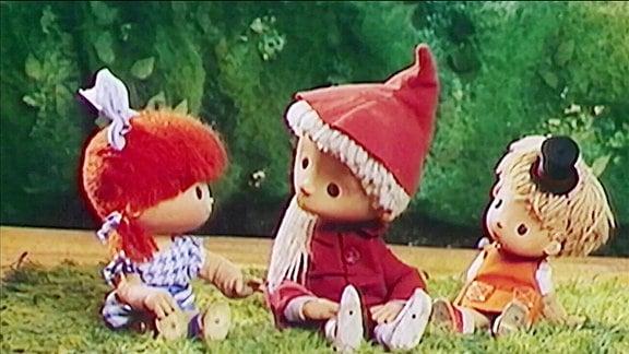 Das Sandmännchen sitzt mit zwei Kindern auf Rasen.