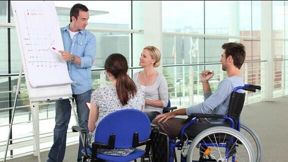 Drei Personen, eine davon im Rollstuhl, sehen auf ein Flipchart.