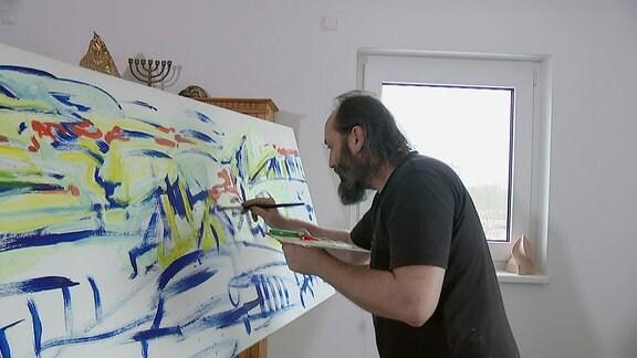 Ein Mann malt an einem Bild