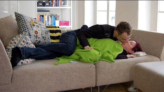 Thomas und Anke liegen auf der Couch und küssen sich