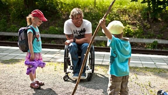 Ein Mann im Rollstuhl neben zwei kleinen Kindern
