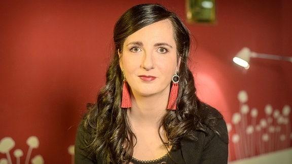 Die Moderatorin Jennifer Sonntag sitzt auf einem Stuhl und schaut in die Kamera. Sie trägt lange, schwarze Haare und rote Ohrringe. Dazu einen schwarzen Pullover.