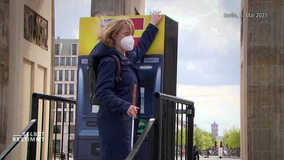 Eine blinde Frau steht vor einem Geldautomat.