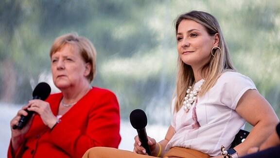 Bundeskanzlerin Angela Merkel (l, CDU) sitzt während des Tages der offenen Tür der Bundesregierung auf der Bühne neben Kristina Vogel, ehemalige deutsche Bahnradsportlerin.