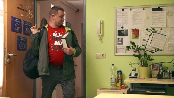 Ein Mann betritt einen Raumen und legt seinen Rucksack ab.