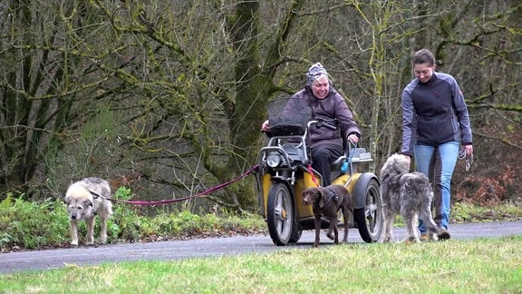 Susanne Müller fährt mit einem Mofa. In ihrer Nähe sind drei Hunde und eine Frau