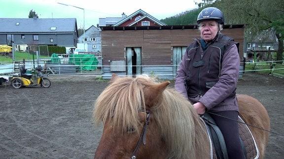 Susanne Müller sitzt auf einem Pferd