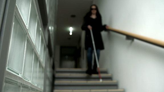 Frau mit Blindenstock auf einer Treppe