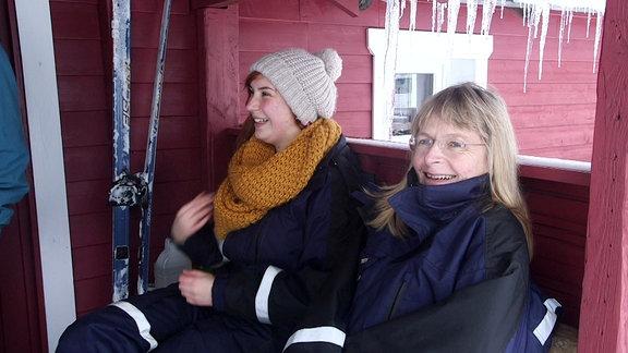 Zwei Frauen sitzen auf der Terasse eine Skihütte.