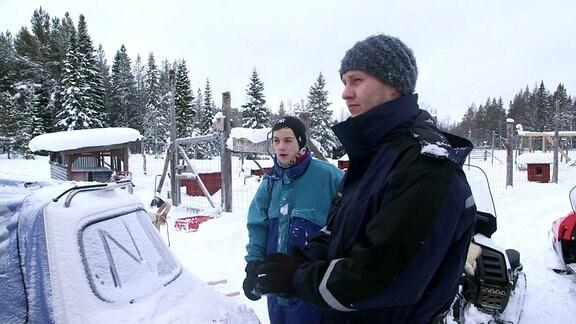 Zwei Personen stehen auf einem verschneiten Hundetrainingsplatz.
